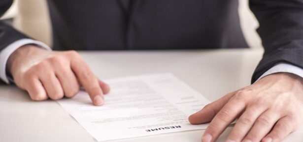 Cropped image of businessman analyzing resume at desk in office.